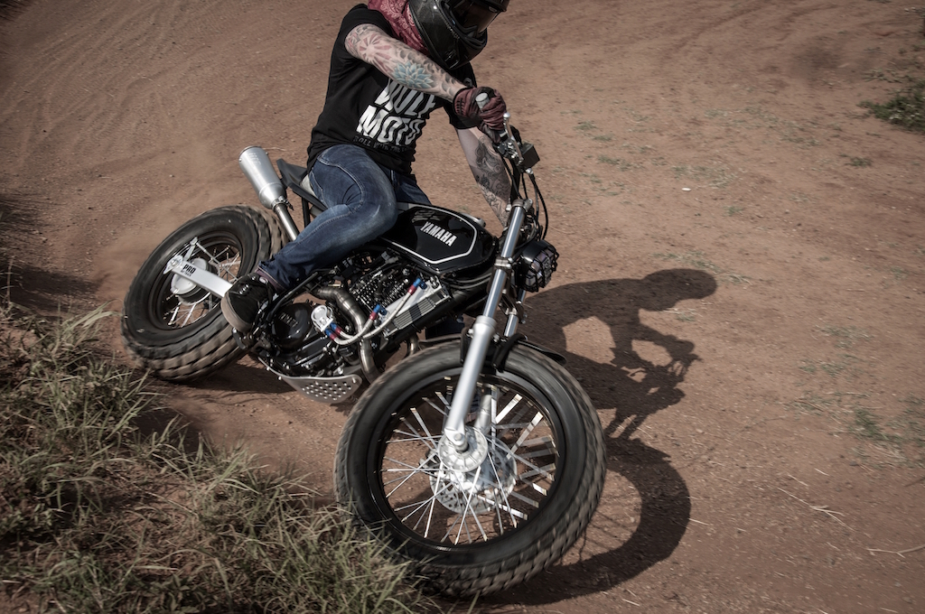"Wolf Moto taking the ""Fat Tracker"" around a dirt corner."