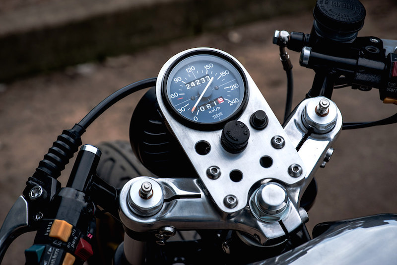 Custom fabricated speedo housing with ignition key and trip reset.